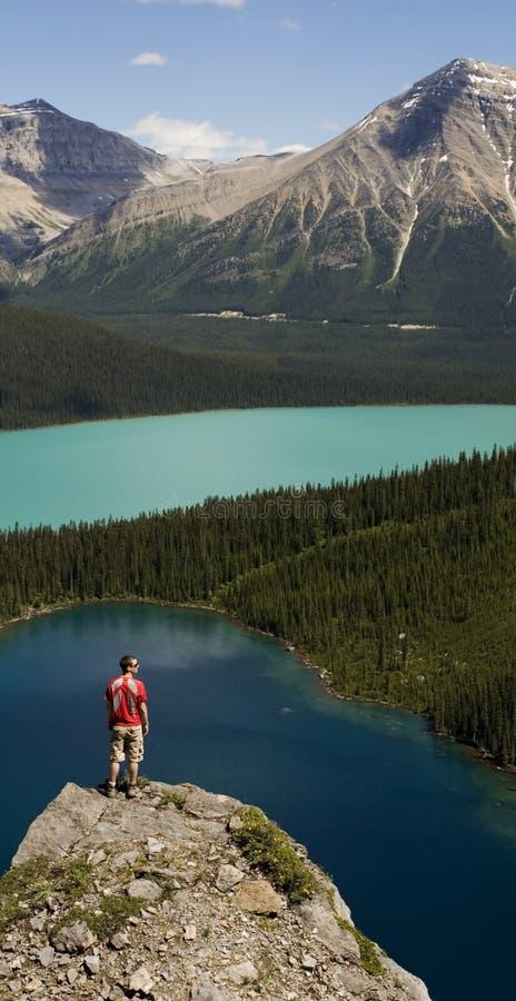 Jonge mens die zich op kei boven meren bevindt royalty-vrije stock foto