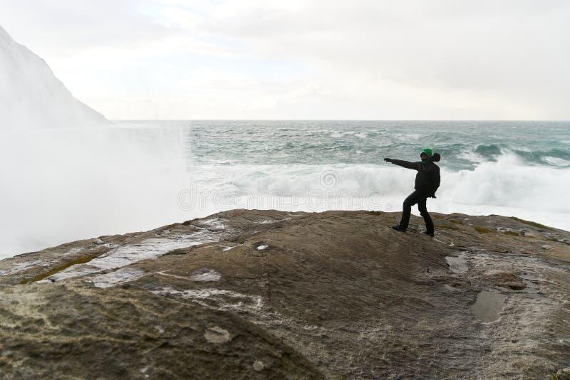 Jonge mens die zich op klippen voor de wilde oceaan met golven bevinden die tegen de rotsen bij Bunes-Strand op Lofoten-Eilanden  royalty-vrije stock foto's