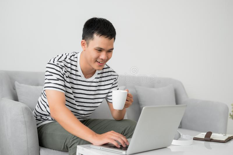 Jonge mens die zich op laptop het computerscherm concentreren, zittend bij bureau in woonkamer, die mok houden stock fotografie
