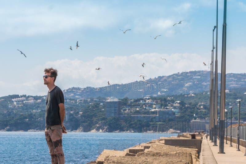 Jonge mens die zich op overzeese pijler in haven en het vooruitzien bevinden Zeemeeuwen en meeuwen in hemel Mediterrane lijn, Pal stock foto