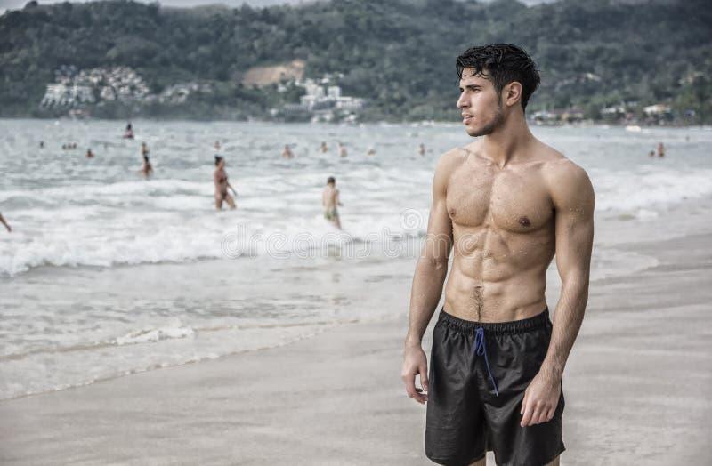 Jonge mens die zich op rand van de oceaan bevinden royalty-vrije stock afbeeldingen