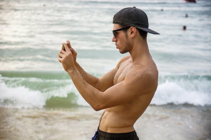 Jonge mens die zich op rand van de oceaan bevinden royalty-vrije stock afbeelding