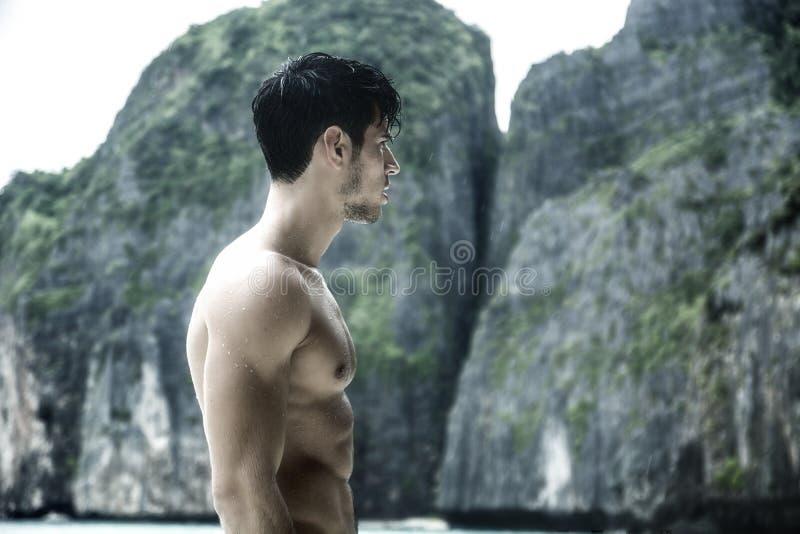 Jonge mens die zich op rand van de oceaan bevinden stock afbeelding
