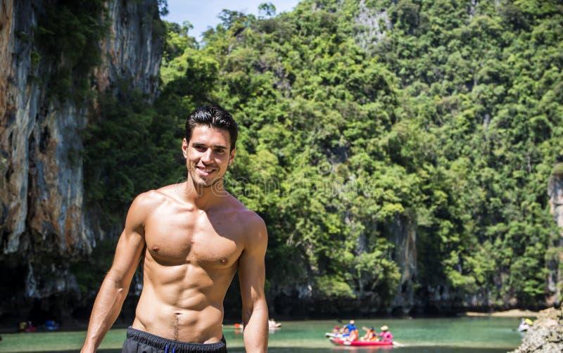 Jonge mens die zich op rand van de oceaan bevinden royalty-vrije stock foto
