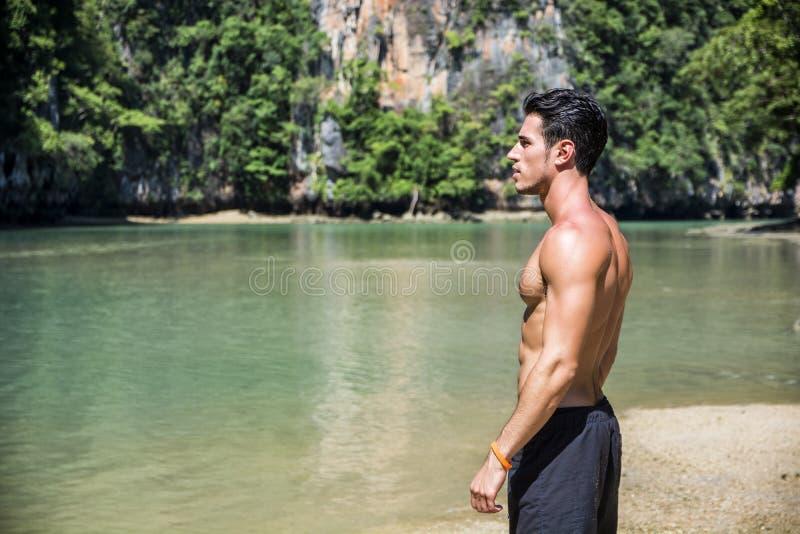 Jonge mens die zich op rand van de oceaan bevinden royalty-vrije stock foto's