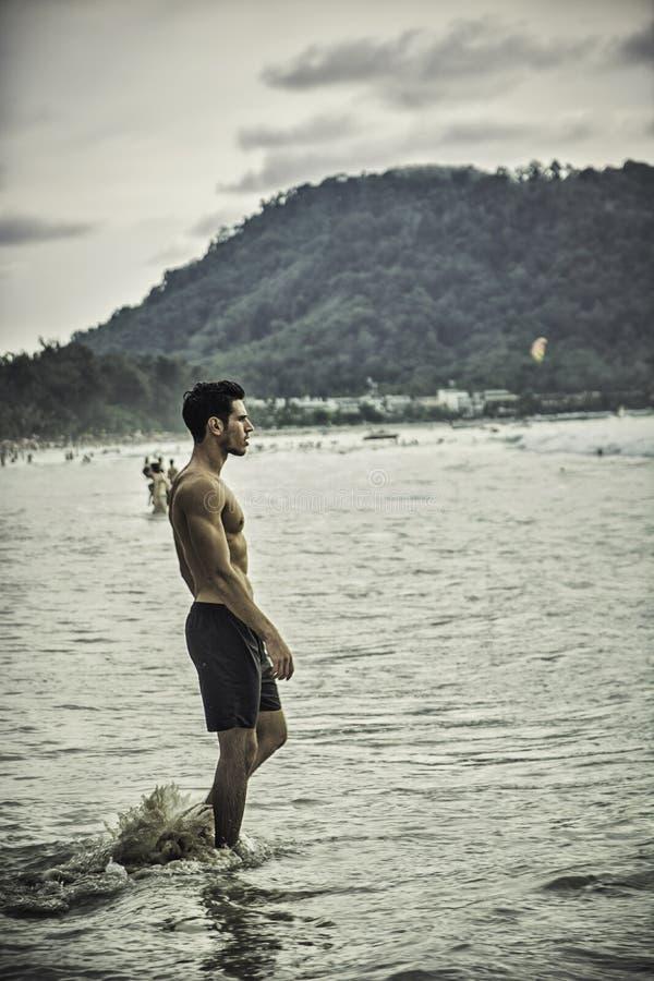 Jonge mens die zich op strand door de oceaan bevinden stock afbeelding