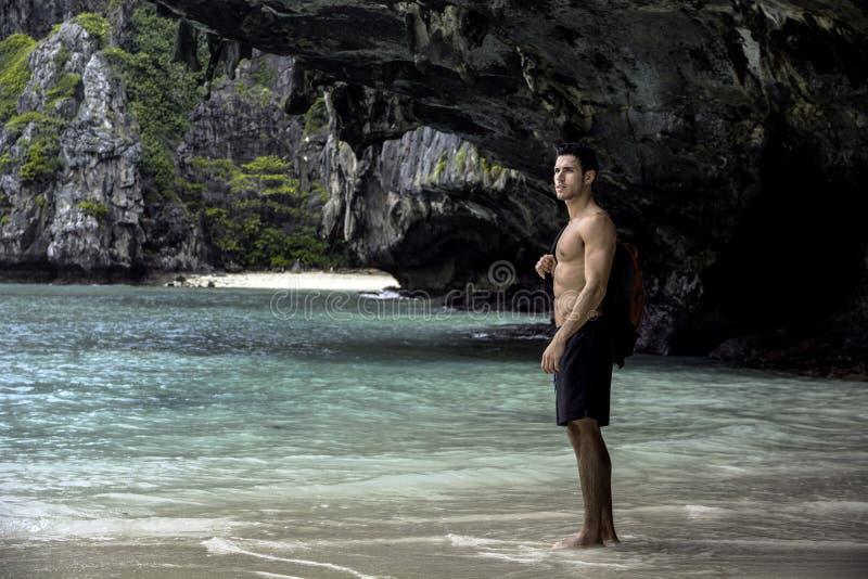 Jonge mens die zich op strand door de oceaan bevinden stock foto
