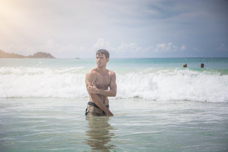 Jonge mens die zich op strand door de oceaan bevinden royalty-vrije stock afbeeldingen