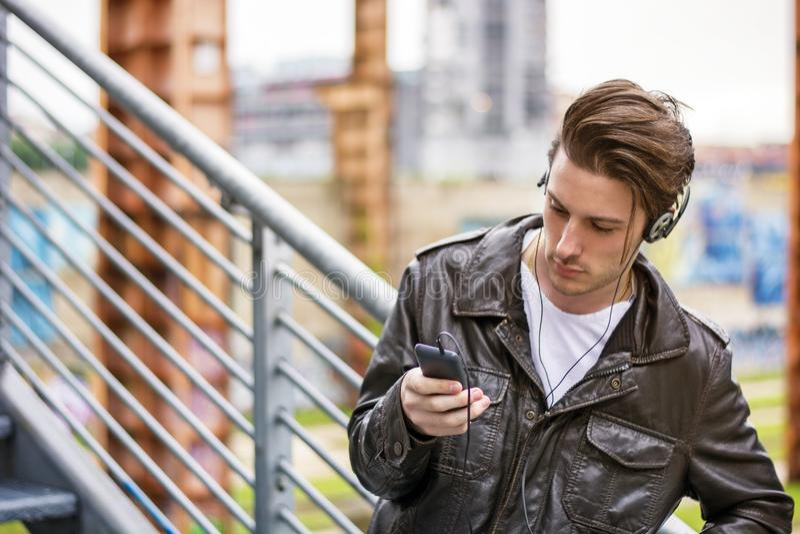 Jonge mens die zich in openlucht in het stedelijke plaatsen bevinden stock afbeelding