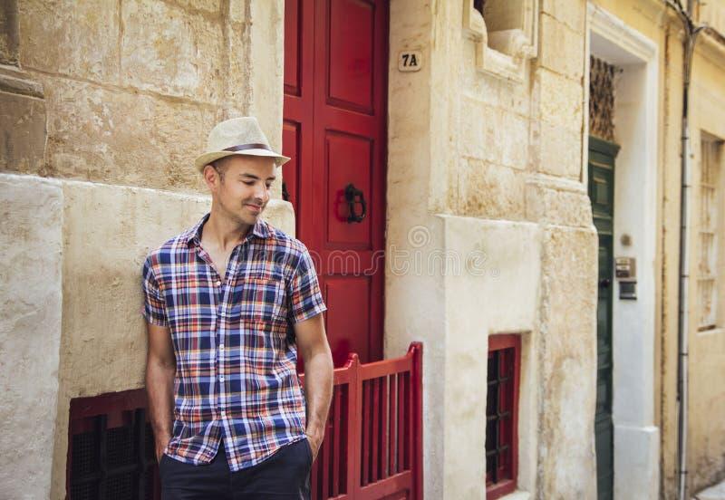 Jonge mens die zich in oude straat in Malta bevinden stock afbeelding