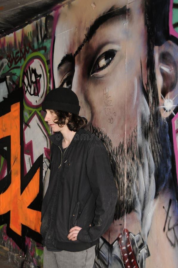 Jonge mens die zich tegen die een muur bevinden met graffiti van een mannelijk gezicht wordt behandeld stock foto