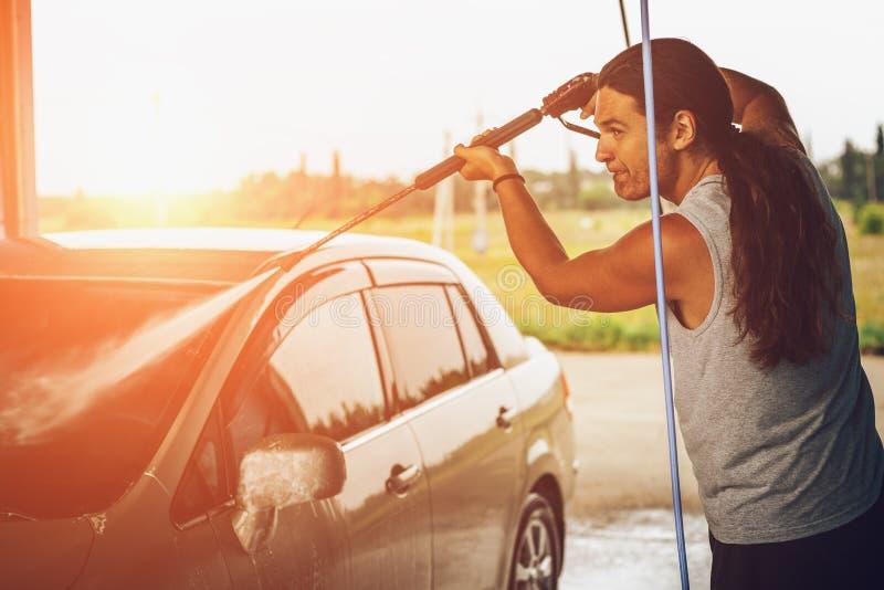 Jonge mens die zijn auto wassen bij autowasserette, zonsondergangeffect royalty-vrije stock fotografie