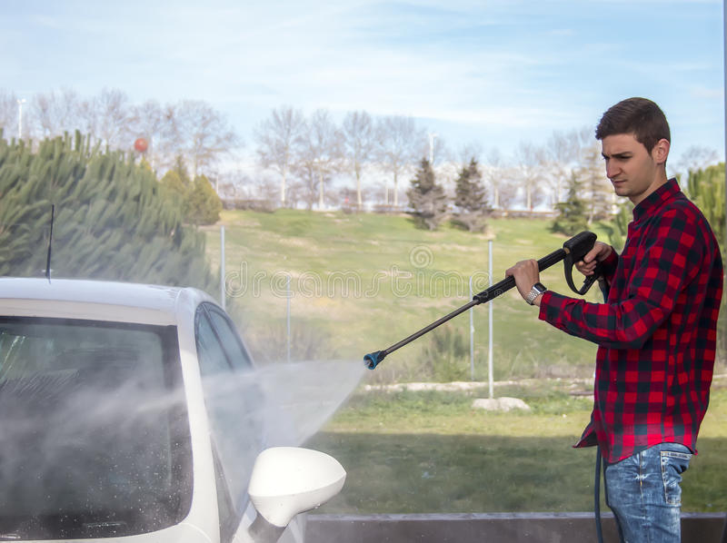 Jonge mens die zijn auto wassen bij drukautowasserette royalty-vrije stock foto's