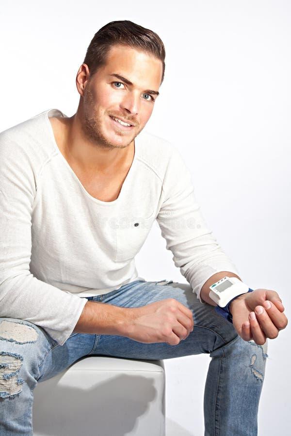 Jonge mens die zijn bloeddruk meten royalty-vrije stock foto