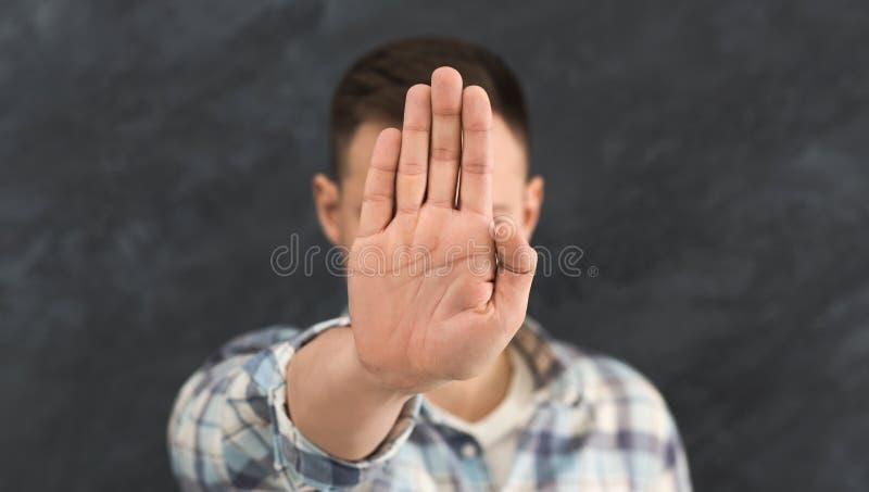 Jonge mens die zijn gezicht met hand verbergen stock afbeelding