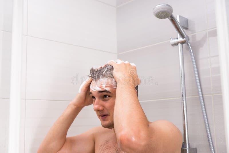 Jonge mens die zijn haar in douche wassen royalty-vrije stock foto