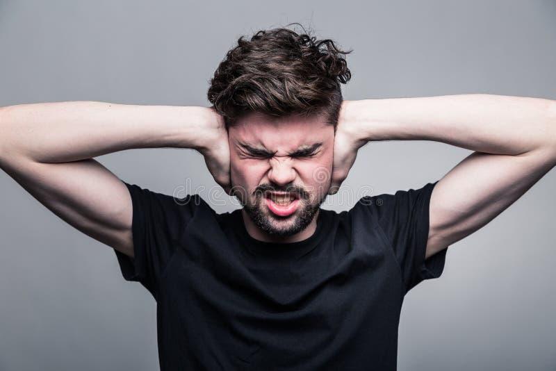 Jonge mens die zijn orenhanden behandelen royalty-vrije stock foto