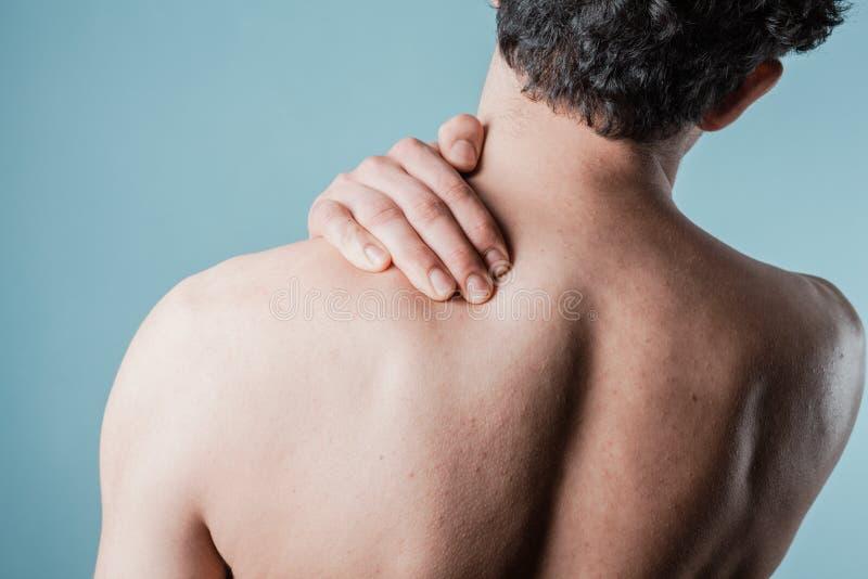 Jonge mens die zijn pijnlijke hals masseren stock foto's