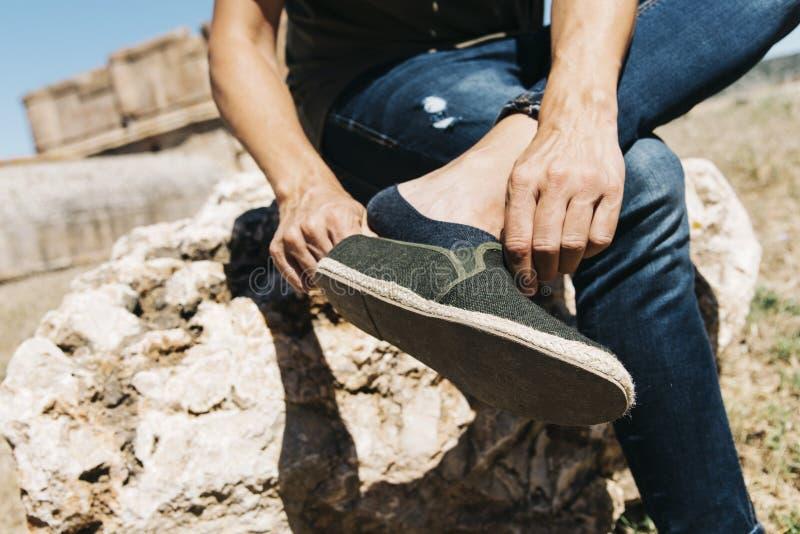 Jonge mens die of zijn schoen aanzetten opstijgen stock fotografie