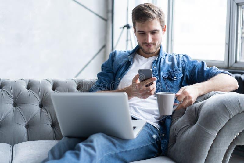 Jonge mens die zijn smartphone voor online bankwezen gebruiken - zitting op bank met laptop op sprong stock fotografie