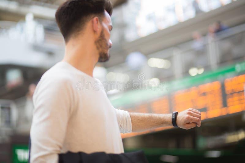 Jonge mens die zijn smartwatch controleren stock foto's