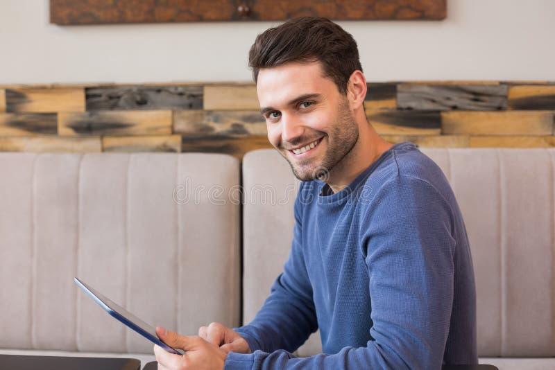 Jonge mens die zijn tabletpc met behulp van stock afbeelding