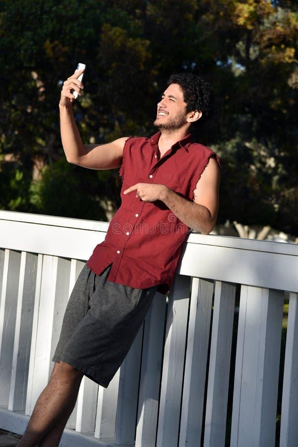 Jonge mens die zijn telefoon het lachen bekijken stock afbeeldingen