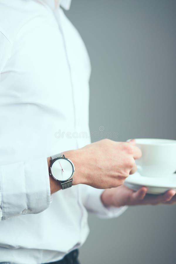 Jonge mens die zilveren polshorloge en wit duidelijk overhemd dragen holdin royalty-vrije stock fotografie