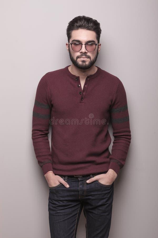 Jonge mens die zonnebril en een sweater van Bourgondië dragen stock fotografie