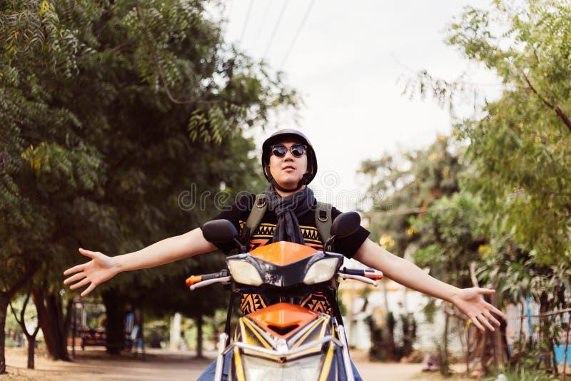 Jonge mens die in zonnebril en helm berijdende motorfiets handen opheffen omhoog als winnaar en succes royalty-vrije stock foto