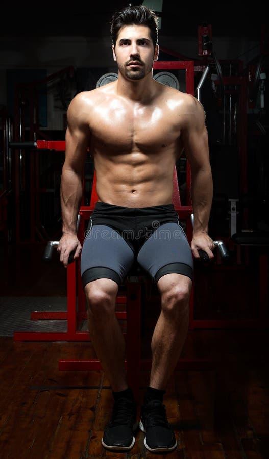 Jonge mens die zwaargewicht oefening in gymnastiek doen stock afbeelding