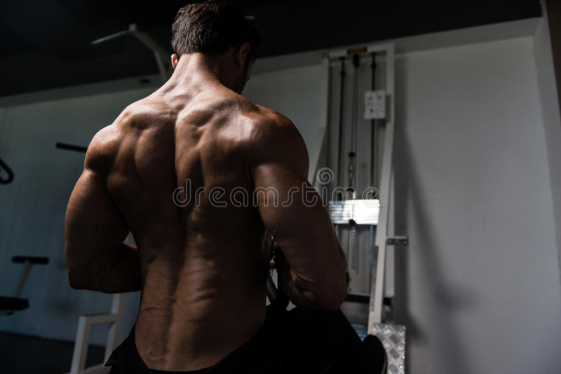 Jonge mens die zwaargewicht oefening voor rug doen stock foto