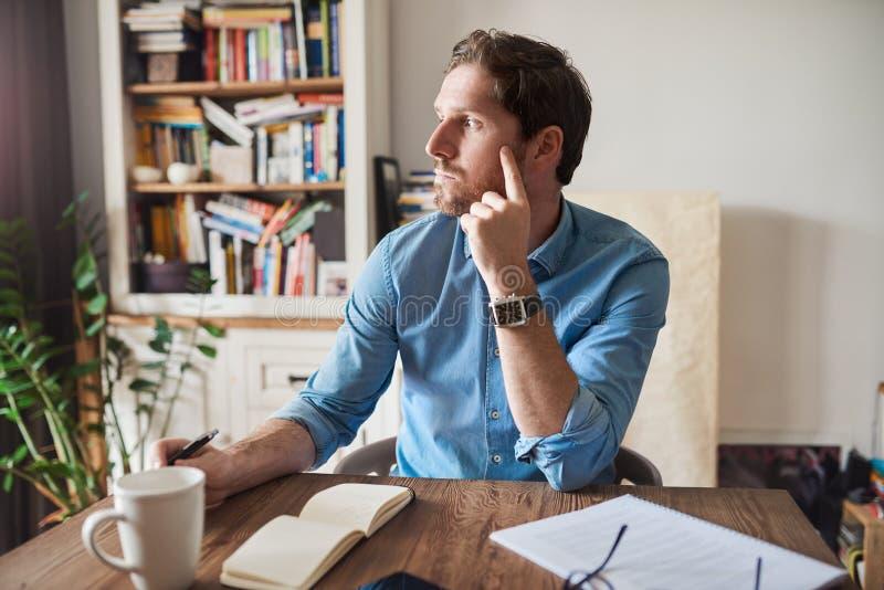 Jonge mens diep in gedachte terwijl het werken van huis stock fotografie