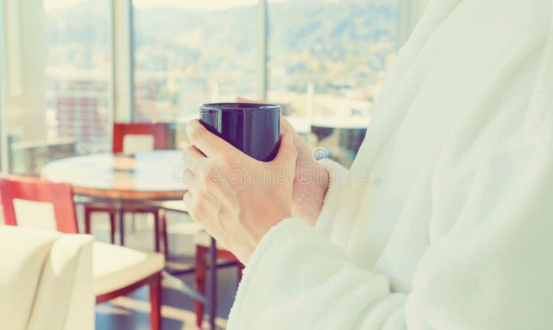 Jonge mens in een badjas met een kop van koffie royalty-vrije stock fotografie