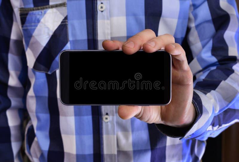 Jonge mens in een blauw plaidoverhemd die een telefoon met zwart s houden stock foto's