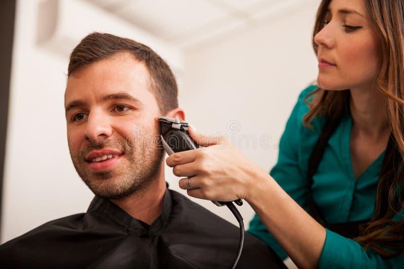 Jonge mens in een haarsalon stock afbeelding