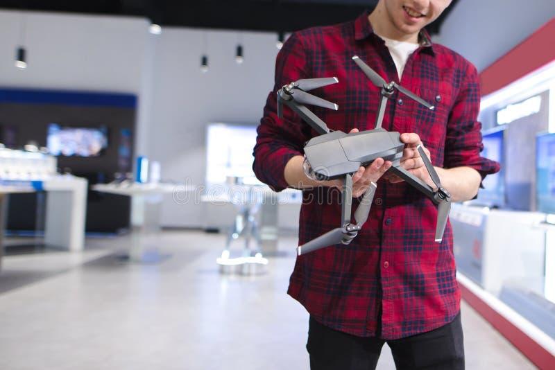 Jonge mens in een hommelsopslag Quadcopter in de handen Een jonge mens koopt een hommel in een technologie-opslag royalty-vrije stock afbeelding