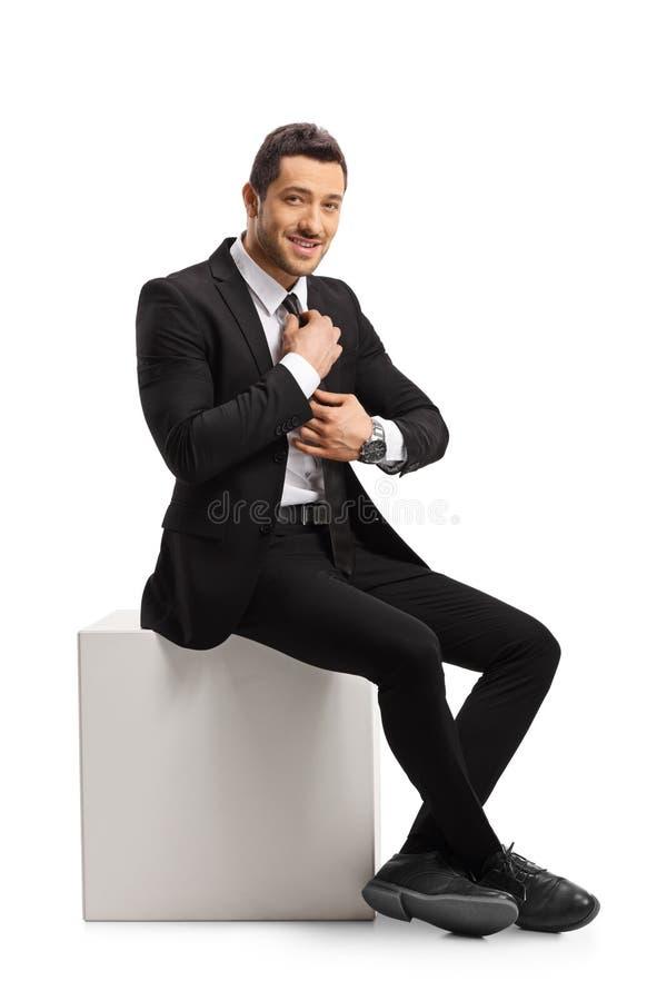 Jonge mens in een kostuum die en zijn band zitten bevestigen royalty-vrije stock fotografie