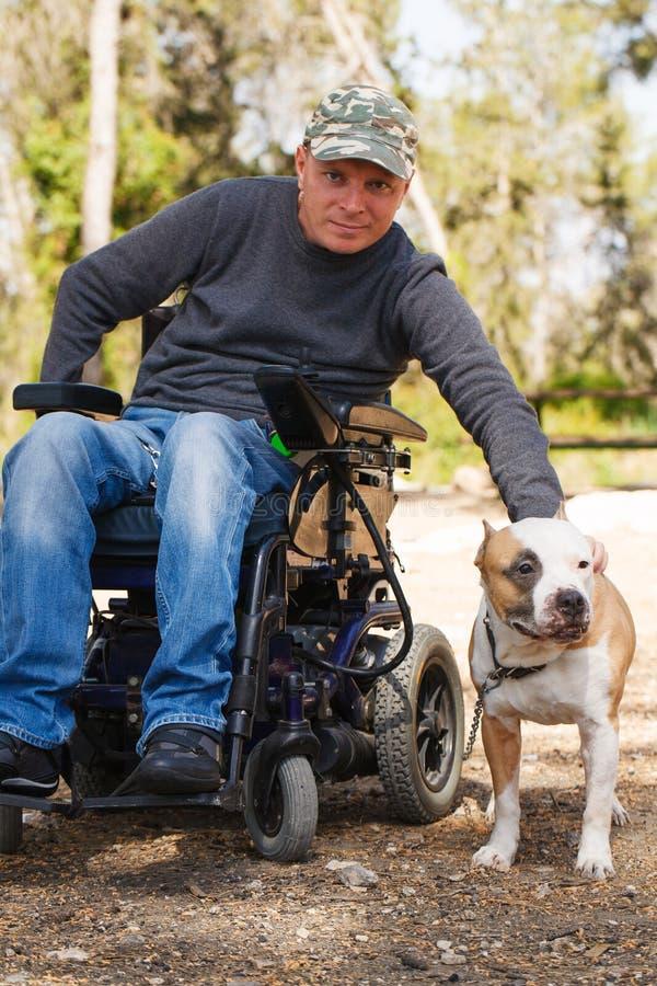 Jonge mens in een rolstoel met zijn gelovige hond. stock fotografie