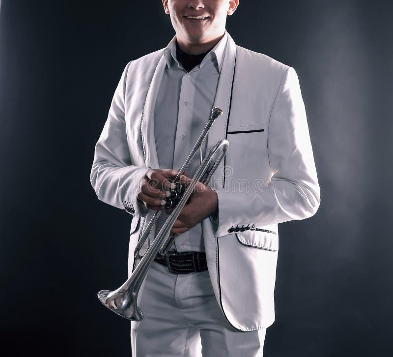 Jonge mens in een wit kostuum met een trompet Ge?soleerde op zwarte achtergrond stock foto