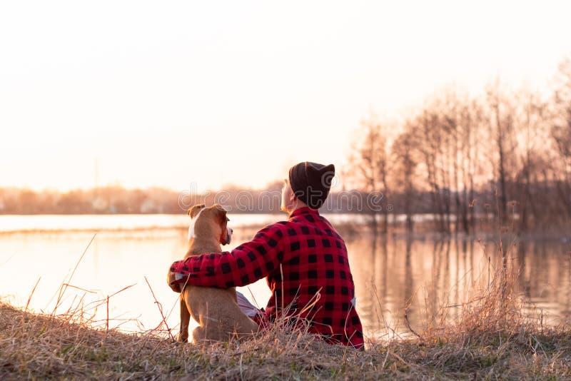 Jonge mens en huisdieren de hond zit door meer bij zonsondergang in de lente of de herfst stock afbeeldingen