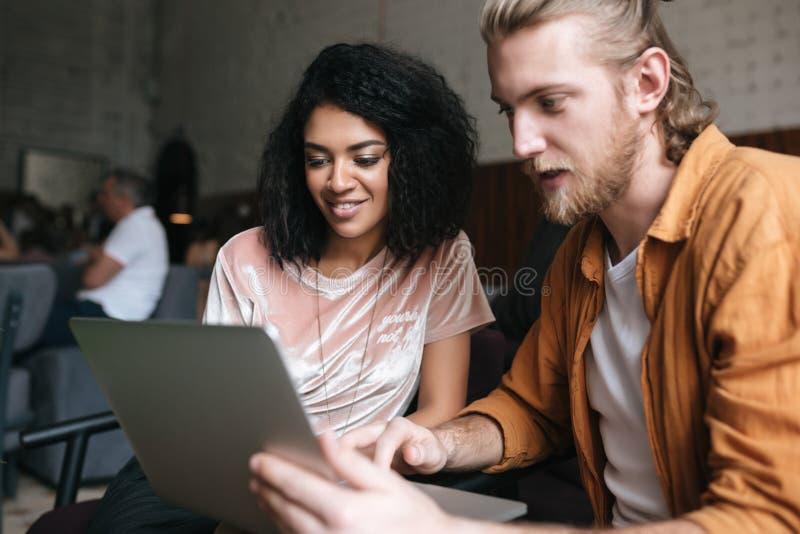 Jonge mens en meisjeszitting in restaurant en het werken aan laptop Glimlachend Afrikaans Amerikaans meisje met donker krullend h royalty-vrije stock foto