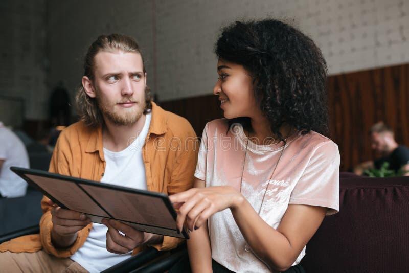 Jonge mens en meisjeszitting in restaurant met menu in handen Vrij Afrikaans Amerikaans meisje met donker krullend haar en jongen royalty-vrije stock foto