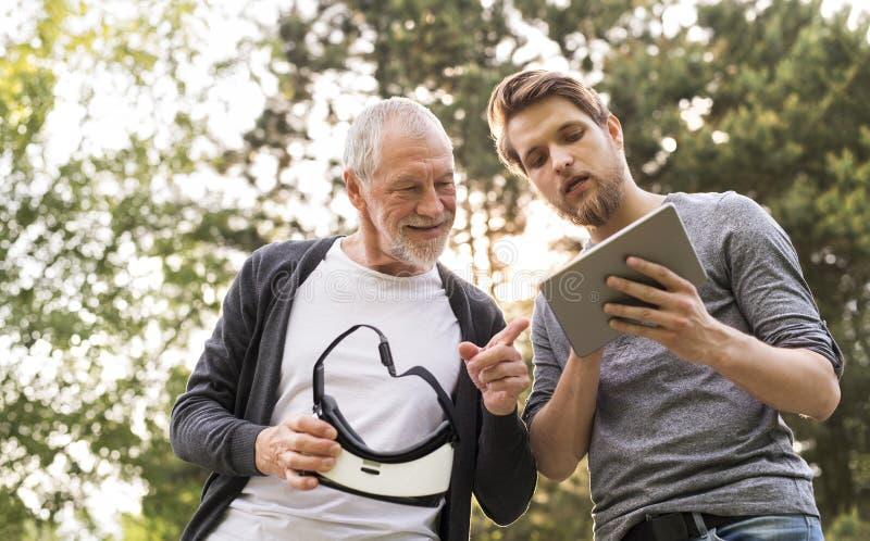 Jonge mens en zijn hogere vader met VR-glazen in openlucht royalty-vrije stock foto's