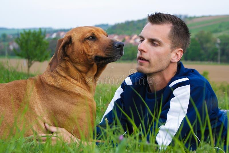 Jonge mens en zijn hond stock afbeeldingen