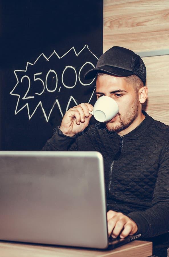 Jonge mens gebruikend laptop en drinkend koffie stock fotografie