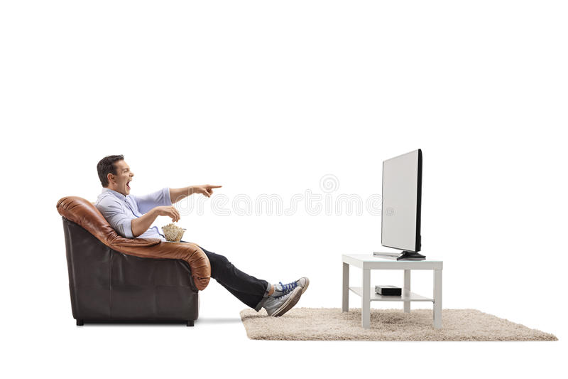 Jonge mens gezet in een leunstoel het letten op televisie en het lachen royalty-vrije stock afbeeldingen
