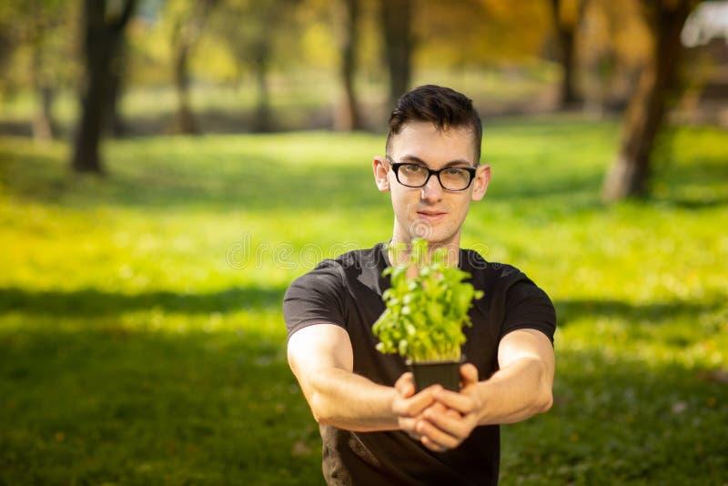 Jonge mens in glazen die in een park en rekhanden met pot van basilicum op groene achtergrond rusten Gezondheidslevensstijl stock foto's