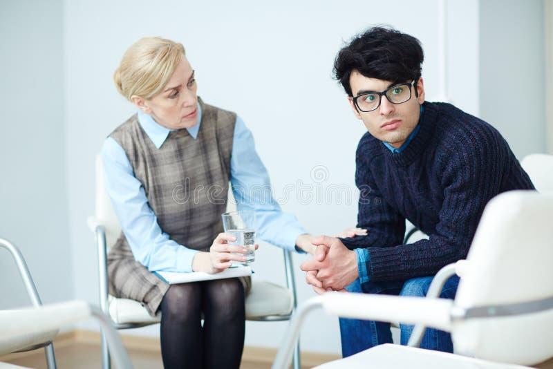 Jonge Mens in het Adviseren Zitting met Psycholoog stock foto's