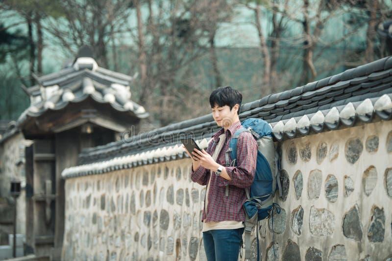 Jonge mens het backpacking in Korea Het gebruiken van een tabletcomputer die tegen een muur leunen royalty-vrije stock fotografie